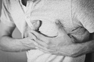 an adult male clutches the left side of his chest in pain - heart attack