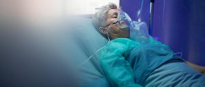 An older female patient lies in a hospital bed wearing an oxygen mask