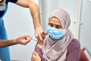 woman in hijab receives covid-19 vaccination